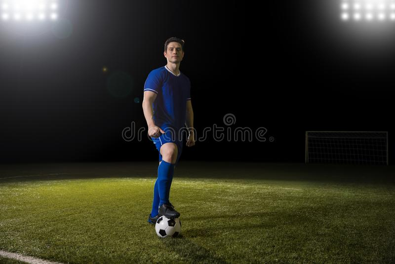 Jogador de futebol com a bola no campo de futebol imagem de stock royalty free
