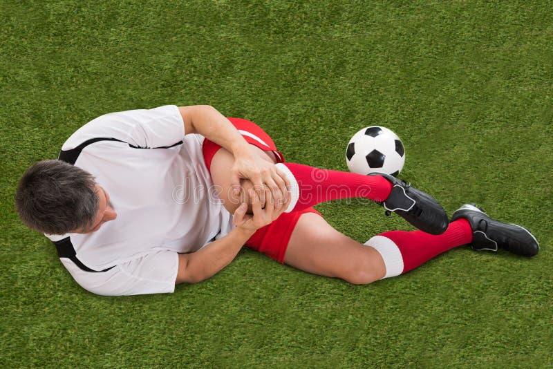 Jogador de futebol com ferimento no joelho fotografia de stock
