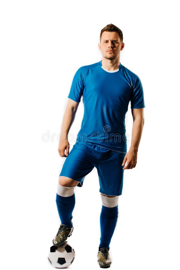 Jogador de futebol considerável novo com um levantamento da bola de futebol isolado no fundo branco foto de stock