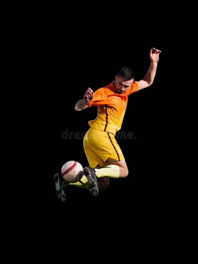Jogador de futebol da atividade na bola de retrocesso vermelha no salto fotografia de stock royalty free