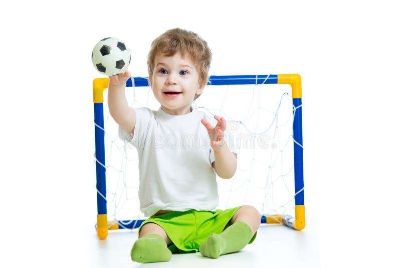 Jogador de futebol da criança que guarda a bola de futebol imagens de stock
