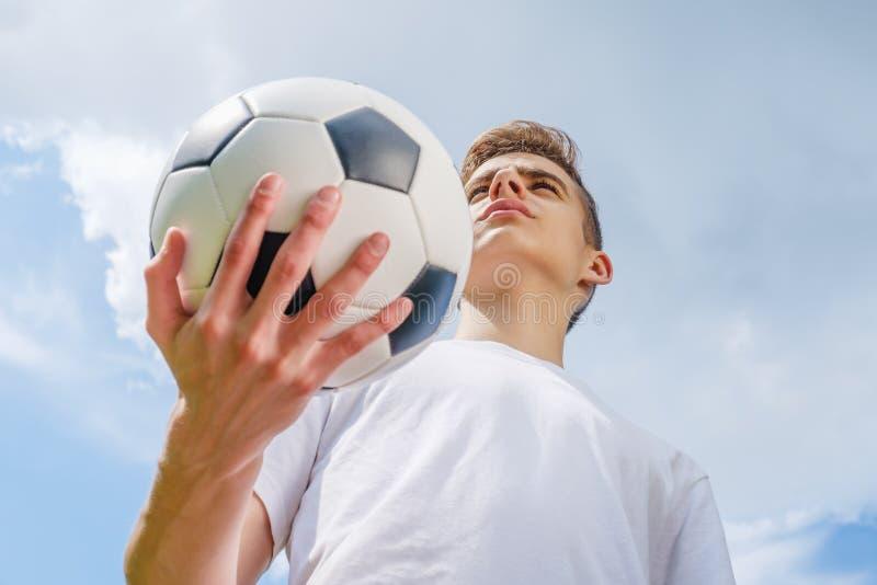 Jogador de futebol da felicidade com bola e o c?u azul fotos de stock royalty free