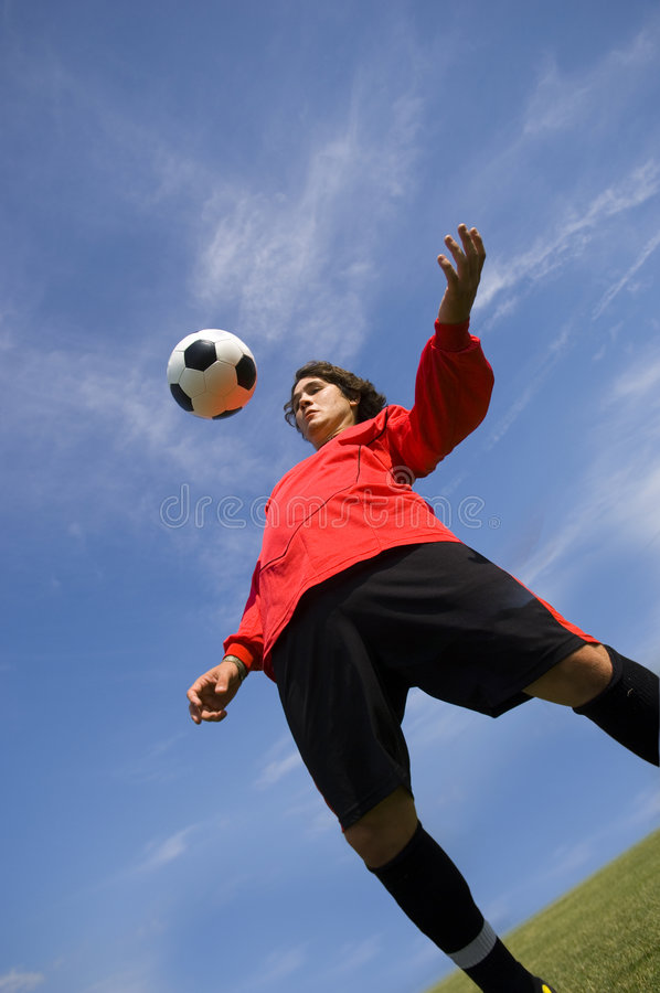 Jogador de futebol do futebol na esfera de controlo vermelha fotos de stock