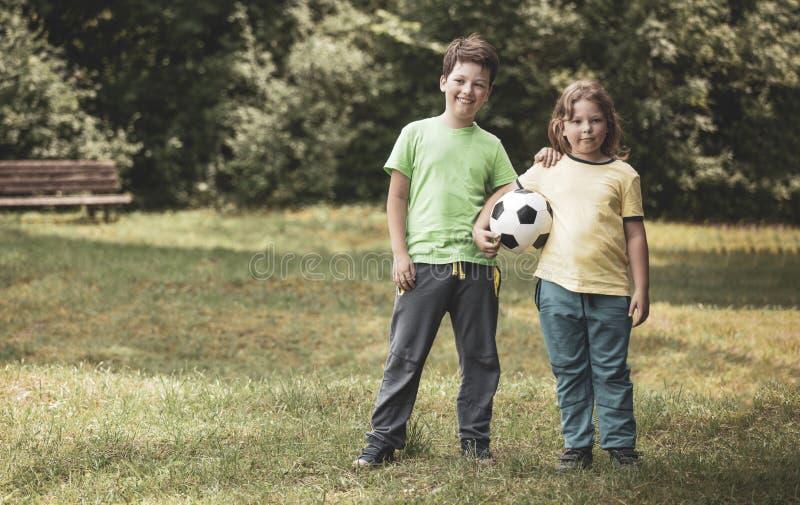 Jogador de futebol de duas crian?as Menino com a bola na grama verde imagem de stock royalty free
