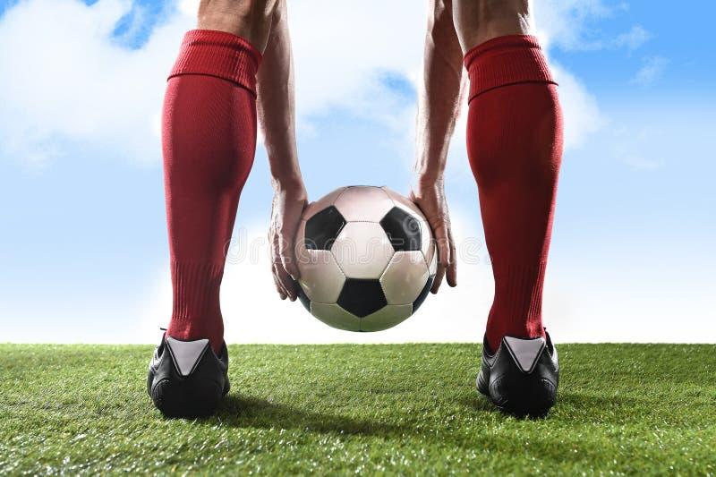 Jogador de futebol em peúgas vermelhas e nas sapatas pretas que guardam a bola em suas mãos que colocam o pontapé ou a pena livre imagem de stock royalty free