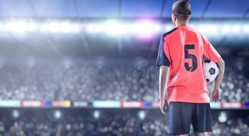 Jogador de futebol fêmea no uniforme vermelho no campo de futebol imagens de stock