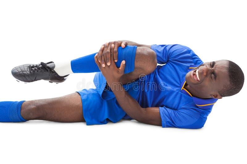 Jogador de futebol ferido que encontra-se na terra fotografia de stock