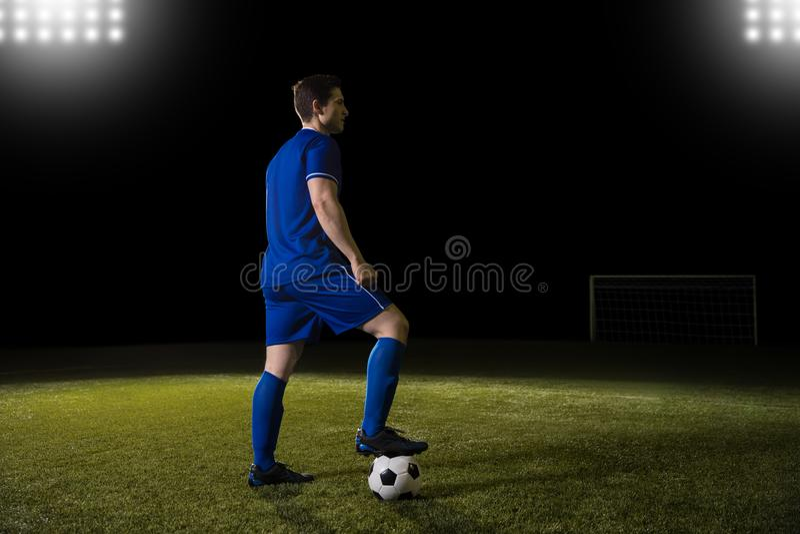 Jogador de futebol masculino com a bola na terra fotografia de stock royalty free
