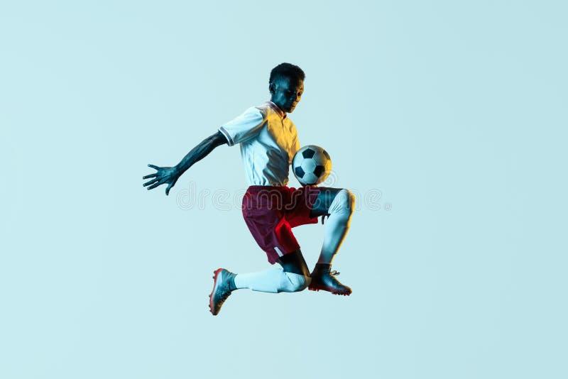 Jogador de futebol masculino que retrocede a bola no salto isolada no fundo do inclina??o imagens de stock