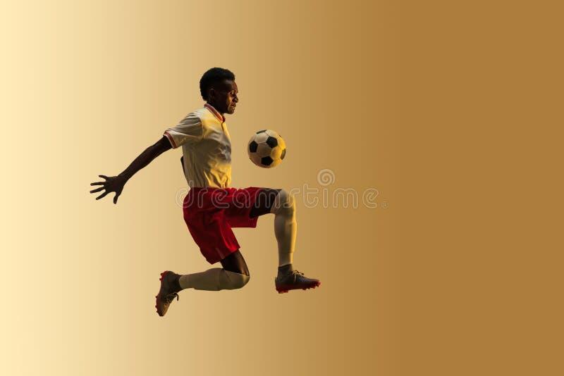 Jogador de futebol masculino que retrocede a bola no salto isolada no fundo do inclina??o fotografia de stock