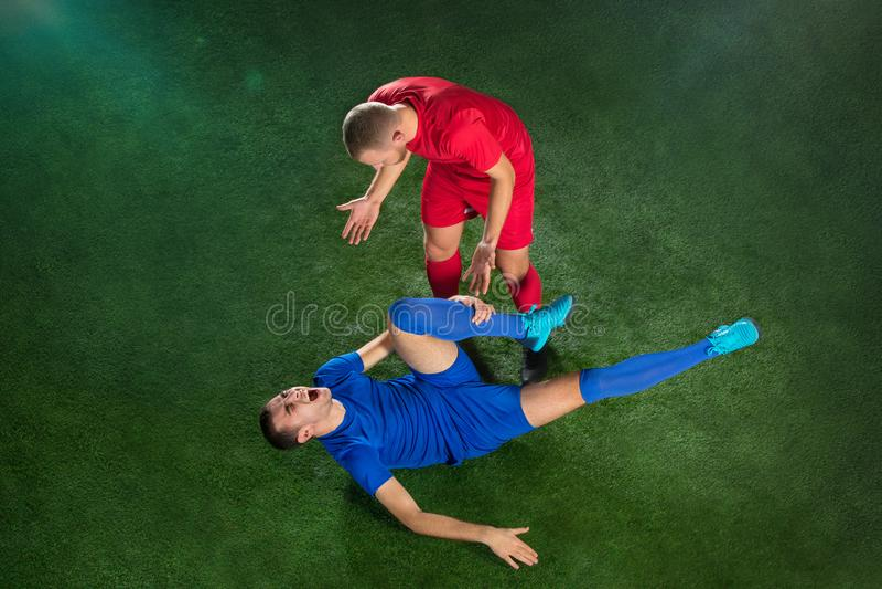 Jogador de futebol masculino que sofre de ferimento de pé no campo do verde do futebol foto de stock