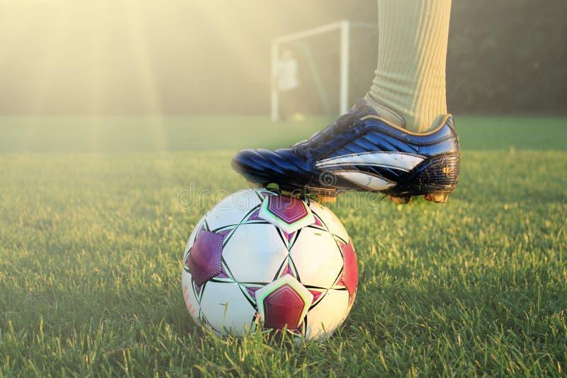 Jogador de futebol na ação com futebol no estádio exterior brilhantemente iluminado Foco no primeiro plano e bola de futebol com  imagens de stock