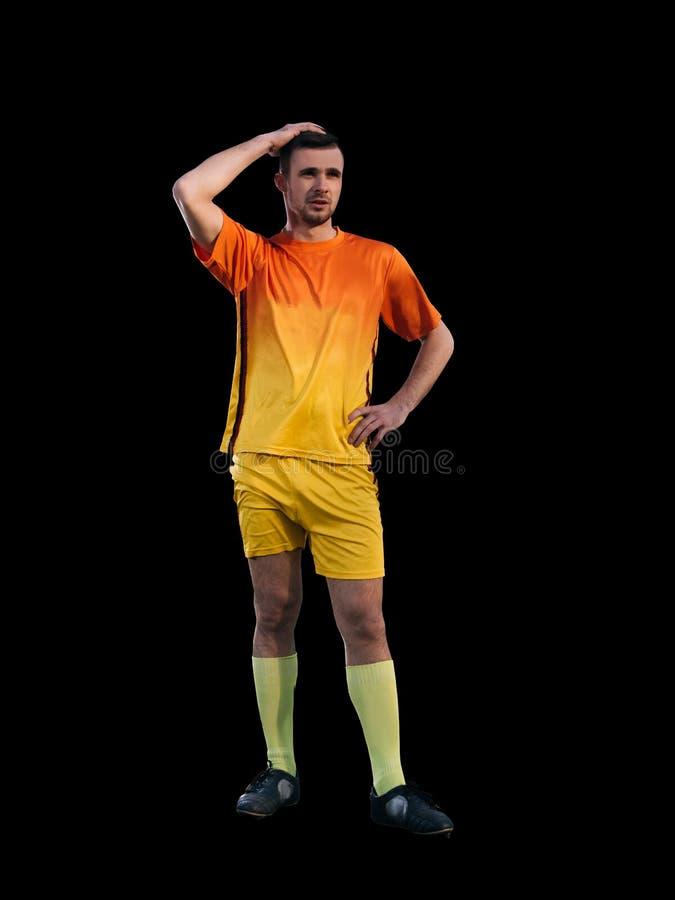 Jogador de futebol na ação no fundo preto imagem de stock royalty free