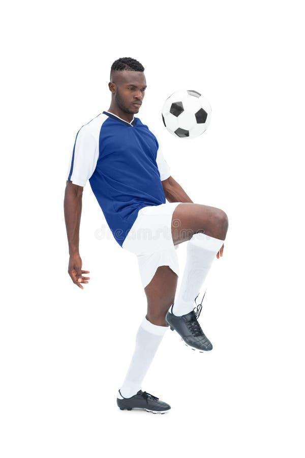 Jogador de futebol na bola de controlo azul do jérsei fotografia de stock royalty free