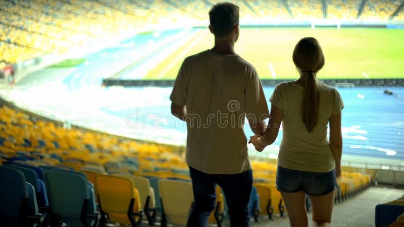 Jogador de futebol na roupa ocasional que mostra a amiga o estádio vazio, datando fotos de stock royalty free