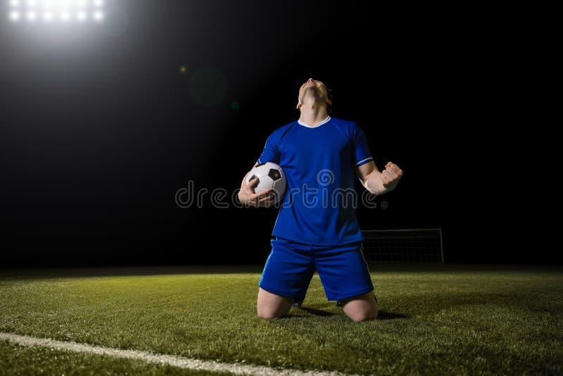 Jogador de futebol que comemora o objetivo no estádio fotos de stock royalty free