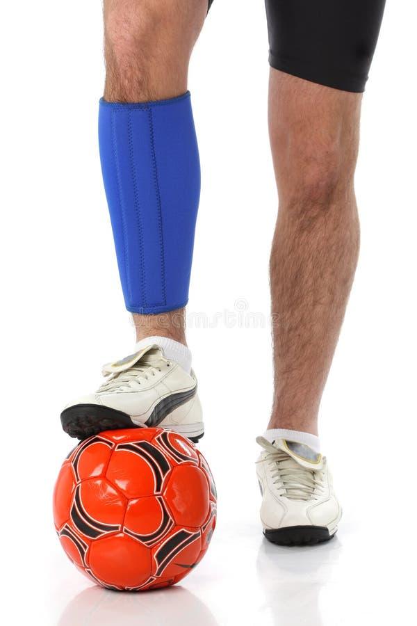Jogador de futebol que desgasta uma cinta do neopreno fotos de stock royalty free