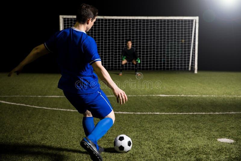 Jogador de futebol que dispara em um pontapé de grande penalidade imagem de stock royalty free