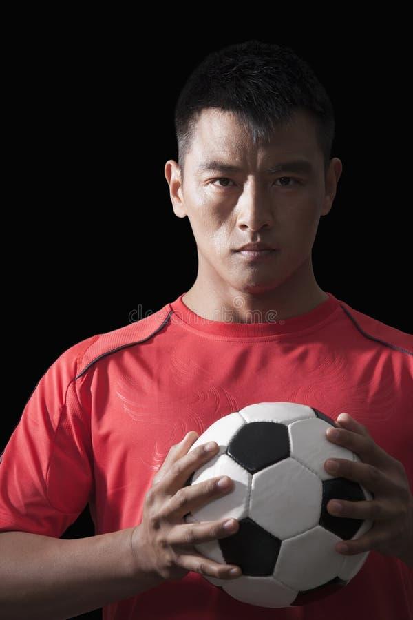Jogador de futebol que guarda a bola à caixa, fundo preto imagem de stock royalty free
