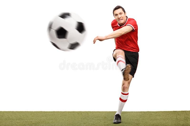 Jogador de futebol que retrocede uma bola na grama imagens de stock