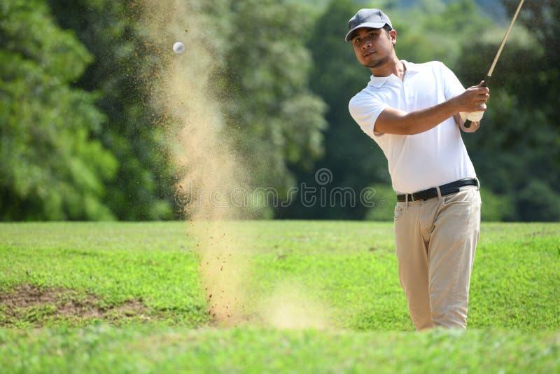 Jogador de golfe asiático novo do homem que bate um tiro do depósito imagem de stock royalty free