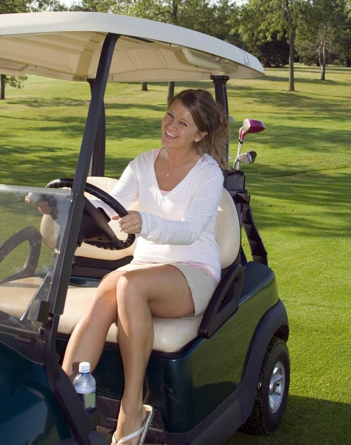 Jogador de golfe da menina no carro fotografia de stock royalty free