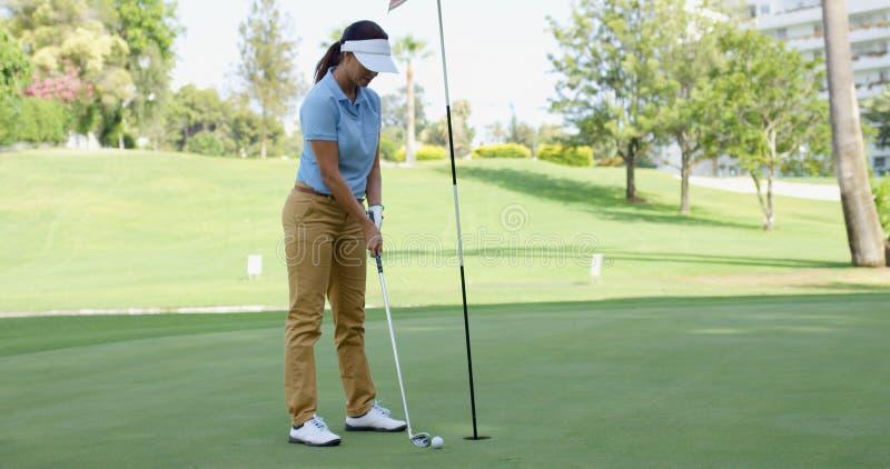 Jogador de golfe da mulher aproximadamente para afundar sua tacada leve foto de stock