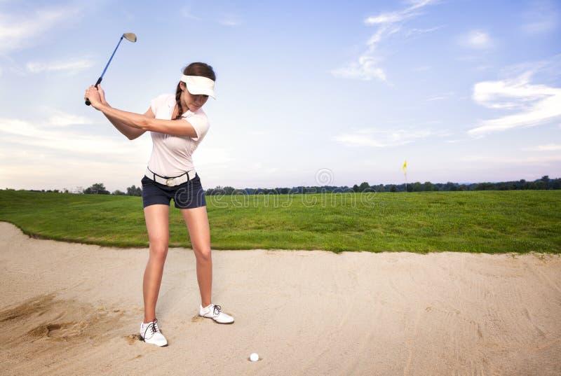 Jogador de golfe da mulher na armadilha de areia que prepara-se para bater a esfera. fotografia de stock royalty free