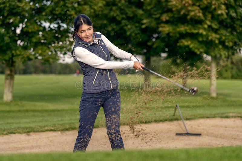 Jogador de golfe da mulher que joga fora de um depósito da areia imagens de stock royalty free