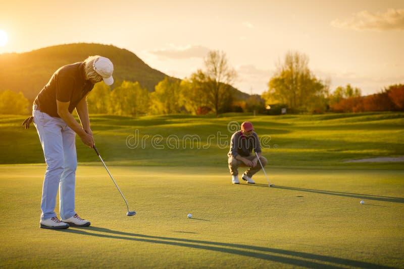 Jogador de golfe de dois sêniores no por do sol imagens de stock royalty free