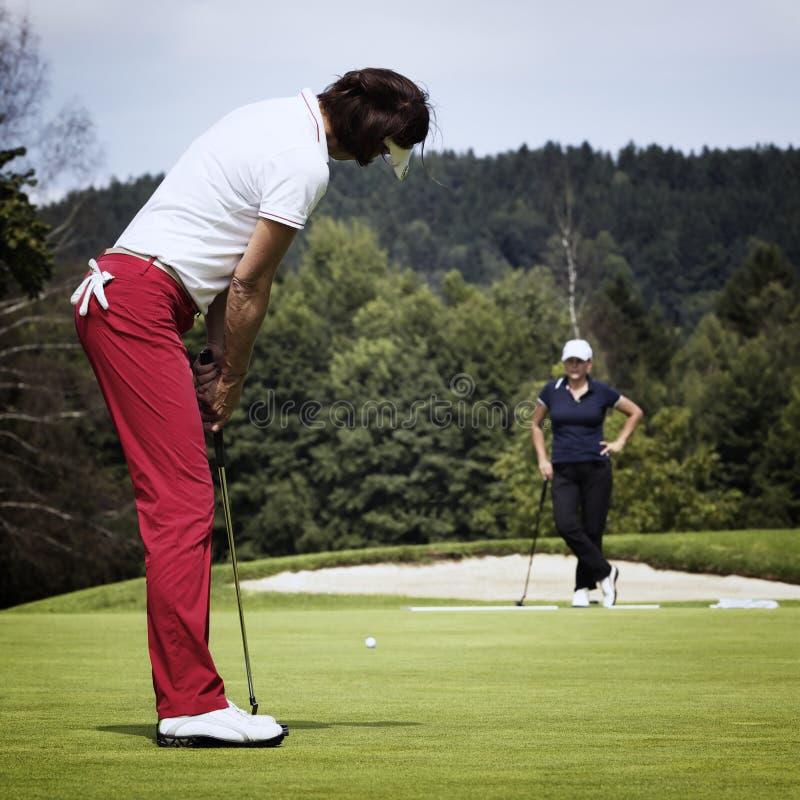 Jogador de golfe de duas fêmeas no verde fotos de stock royalty free