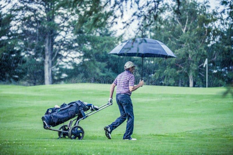 Jogador de golfe em um dia chuvoso que sae do campo de golfe fotos de stock royalty free