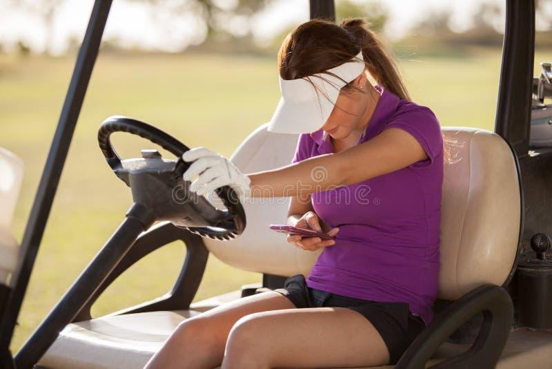 Jogador de golfe fêmea com um telemóvel imagens de stock
