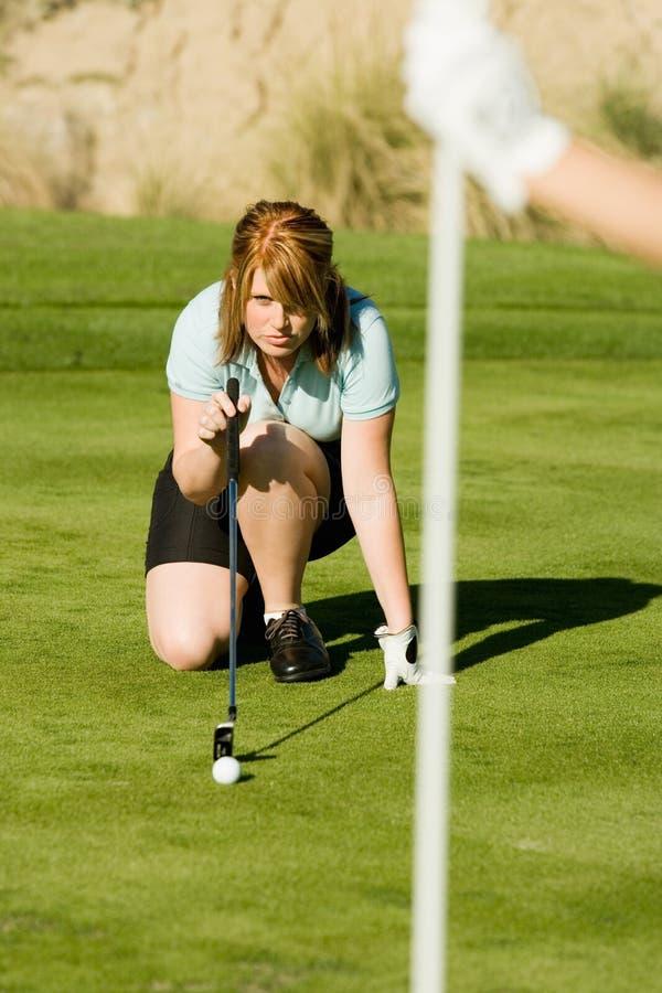 Jogador de golfe fêmea que alinha sua tacada leve foto de stock royalty free
