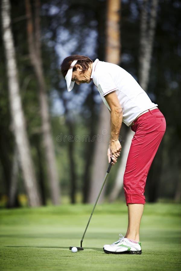 Jogador de golfe fêmea que concentra-se na colocação imagem de stock royalty free