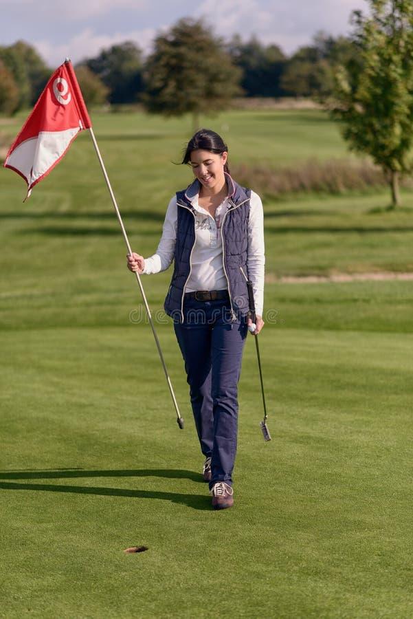 Jogador de golfe fêmea que guarda a bandeira do furo fotografia de stock