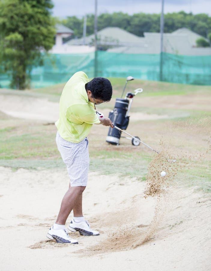 Jogador de golfe masculino que bate a bola de golfe fora de uma armadilha de areia fotos de stock