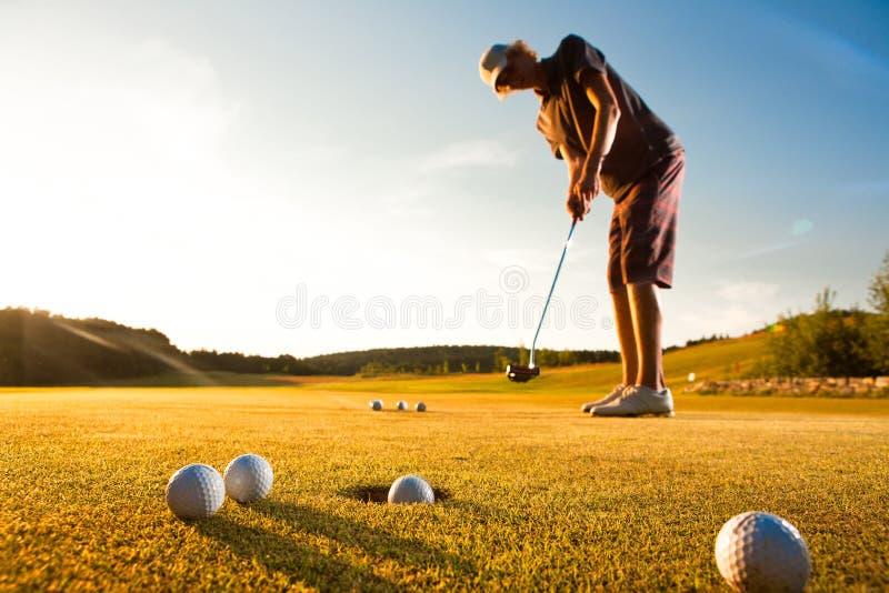 Jogador de golfe masculino que pratica uma paridade durante o por do sol fotografia de stock