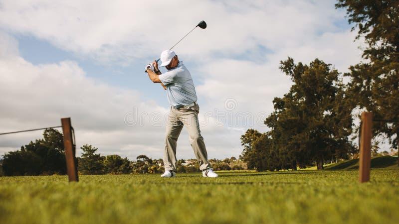 Jogador de golfe masculino superior que toma o tiro imagens de stock