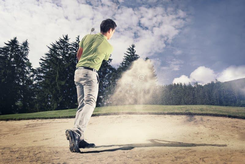Jogador de golfe na armadilha de areia. imagem de stock