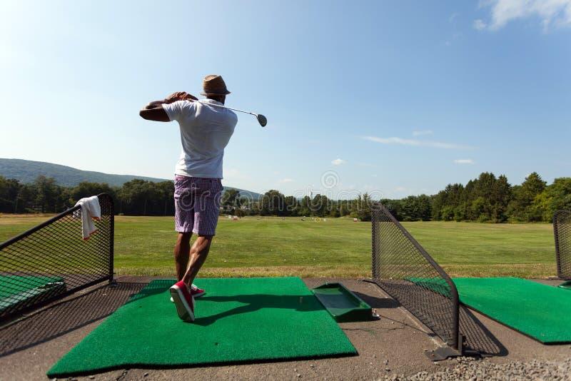 Jogador de golfe no driving range imagens de stock