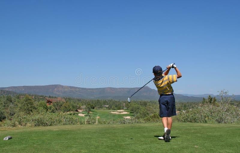 Jogador de golfe novo que bate um tiro de golfe imagem de stock