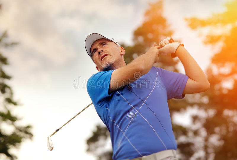 Jogador de golfe que dispara em uma esfera de golfe imagens de stock royalty free