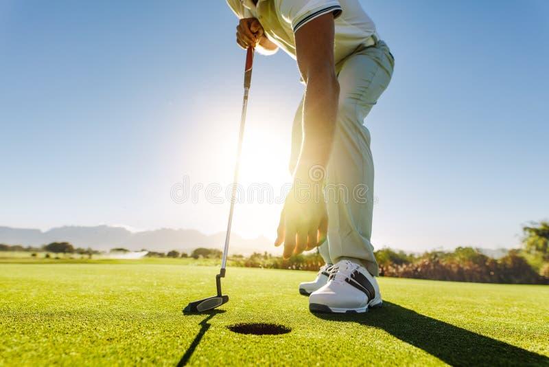 Jogador de golfe que escolhe a bola do furo após posto imagens de stock