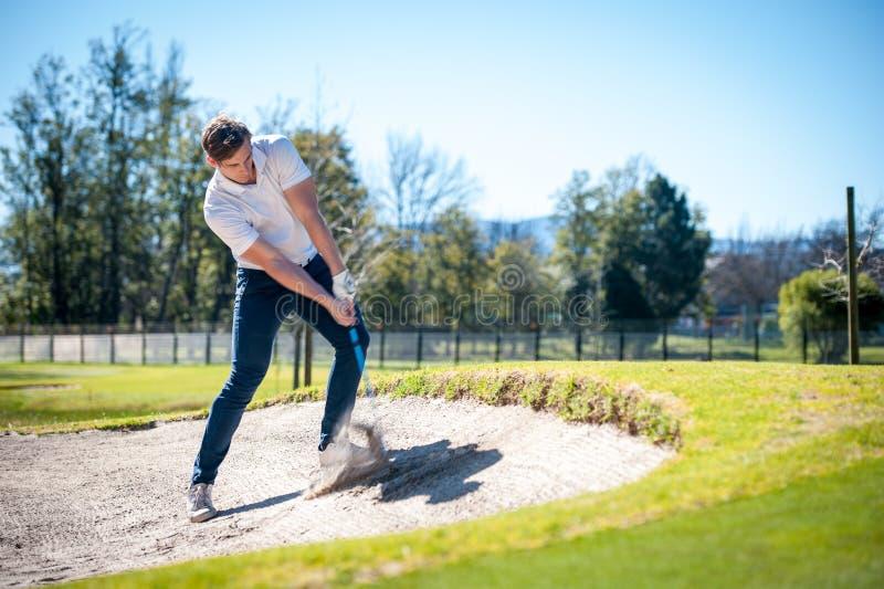 Jogador de golfe que joga um tiro de microplaqueta no verde imagem de stock