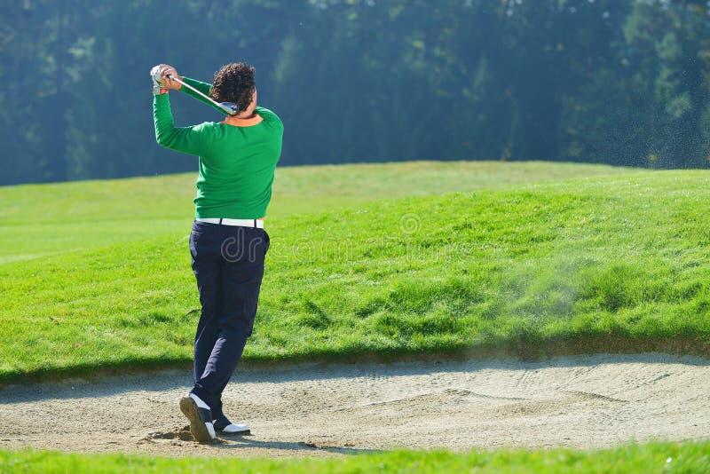 Jogador de golfe que lasca a bola da armadilha de areia fotografia de stock royalty free