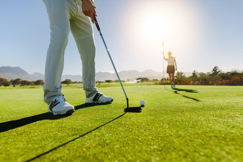 Jogador de golfe que põe a bola com o sócio fêmea que guarda a bandeira sobre o cou do golfe imagens de stock royalty free