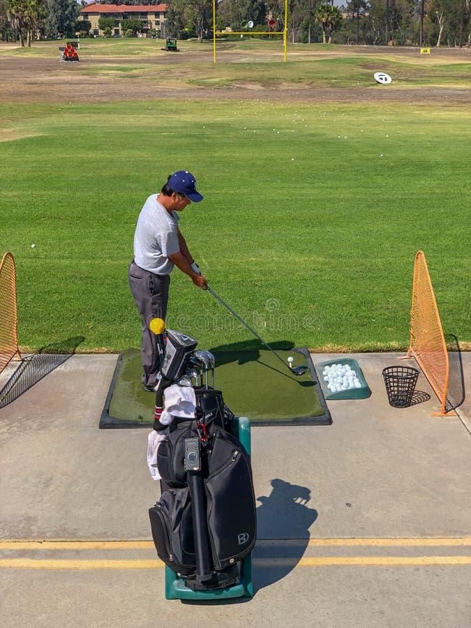 Jogador de golfe que pratica no facilit da prática do driving range do golfe foto de stock
