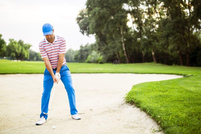 Jogador de golfe que toma um tiro do depósito imagens de stock