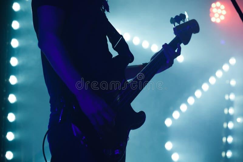 Jogador de guitarra-baixo em luzes azuis da fase fotos de stock royalty free